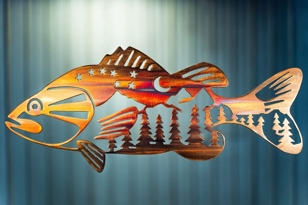 Metal wall art of bass with mountain scene in body.