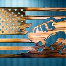 Metal wall art depicting a Jeep climbing a mountain inside an American Flag with a Wood Grain Copper Patina finish on the metal.