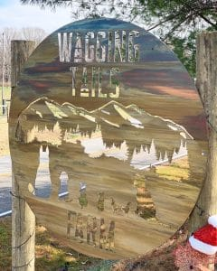 Wagging Tails Farm metal art business sign in Ellijay, GA. Round sign depicts a mountain scene with pine trees in the background and cats, dogs and chickens in the foreground.