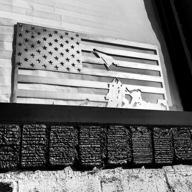 Metal wall art of an American Flag made of metal depicting the image of Raising the Flag at Iwo Jima finished with a Camo Patina. This picture shows the American Flag outside of Artful Ellijay