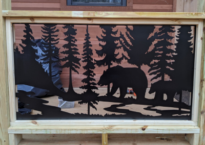 Wooden porch railing with inserts made from metal art with bears, pine trees, river in the foreground and mountains in the background scene.
