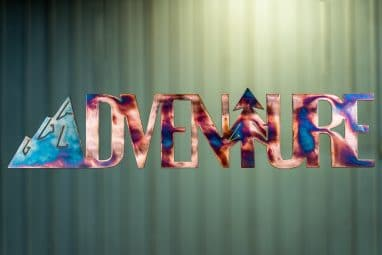 Adventure Metal Wall Art is the word adventure cut out of metal with a mountain for the letter A and a tree for the letter T. This particular metal art piece has a multi-color patina with a torch effect.
