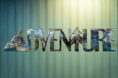 Adventure Metal Wall Art is the word adventure cut out of metal with a mountain for the letter A and a tree for the letter T. This particular piece is finished with a Camo Patina.