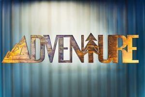 Adventure Metal Wall Art is the word adventure cut out of metal with a mountain for the letter A and a tree for the letter T