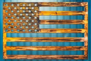 American Flag Metal Art wall decor depicting an American Flag cut out of metal. Picture shows a Wood Grain Copper Patina finish.