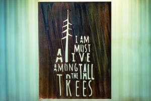 Among the Tall Trees Metal Wall Art is the quote I Am Most Alive Among the Tall Trees cut into metal. This particular piece is finished with a Camo Patina.