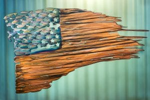 Battled Colors is metal wall art design depicting a tattered American Flag made out of metal. This particular flag has a multi-color patina which highlights the area around the cut out stars blue while the stripes are a deep woodgrain copper look.