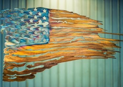 Battled Colors is metal wall art design depicting a tattered American Flag made out of metal. This particular flag has a multi-color patina which highlights the area around the cut out stars blue while the stripes are a woodgrain copper look.