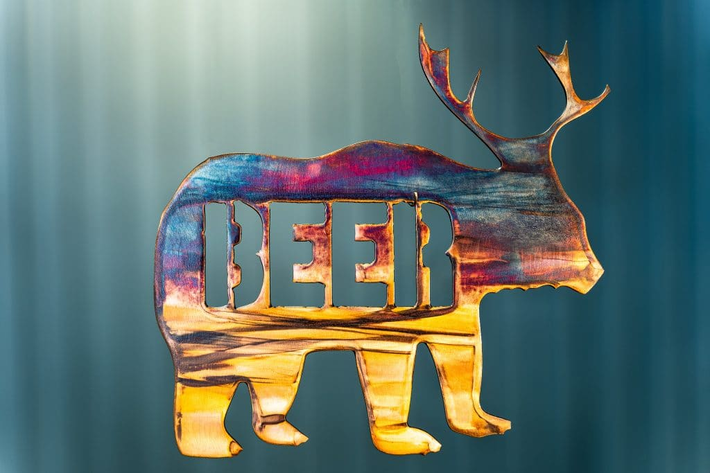 "Metal art of a bear body with deer antlers and the word ""beer"" in the body of the bear - all cut out of metal. This piece has a multi-color patina finish with dark blues and purples up top and golden yellow towards the feet."