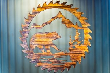 Bear Saw Blade Metal Wall Art depicts a mountain scene with a bear walking on all fours within a saw blade outline. This has a Wood Grain Copper Patina finish with some Multi-Color elements.