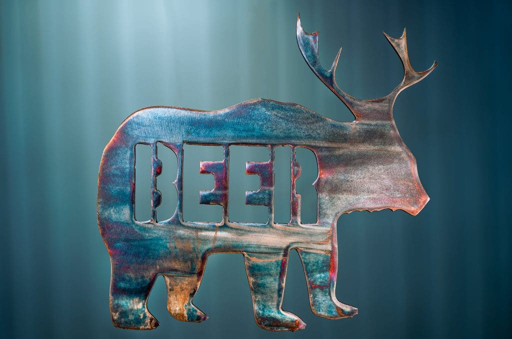 "Metal art of a bear body with deer antlers and the word ""beer"" in the body of the bear - all cut out of metal. This piece has a multi-color patina finish with dark blues and purples throughout the body of the bear."