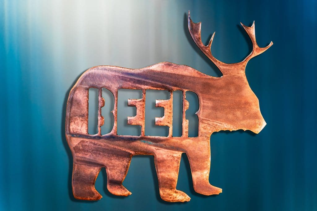 "Metal art of a bear body with deer antlers and the word ""beer"" in the body of the bear - all cut out of metal. This piece has a wood grain copper patina."