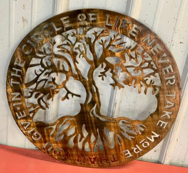 Circular metal wall art with a tree in the middle and the phrase In The Circle of Life Never Give More Than You Take