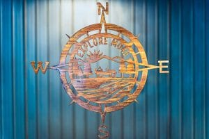 Explore More Compass metal wall decor is a large metal cutout of a compass with a class Jeep in the middle with the phase Explore More. The metal is finished with a wood grain copper patina.