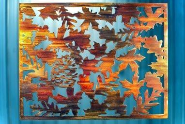 Metal wall art depicting fall leaves on metal cut square.