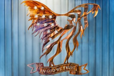 Metal wall art of American Bald Eagle with expanded wings depicting American Flag and holding In God We Trust banner in talons all cut out of metal with a Wood Grain Copper Patina.