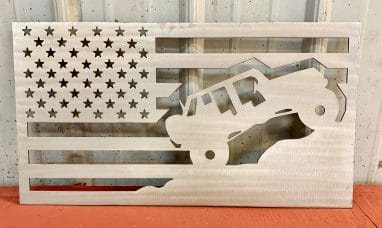 Metal wall art depicting a Jeep climbing a mountain inside an American Flag with a Clear Coat finish on the metal.