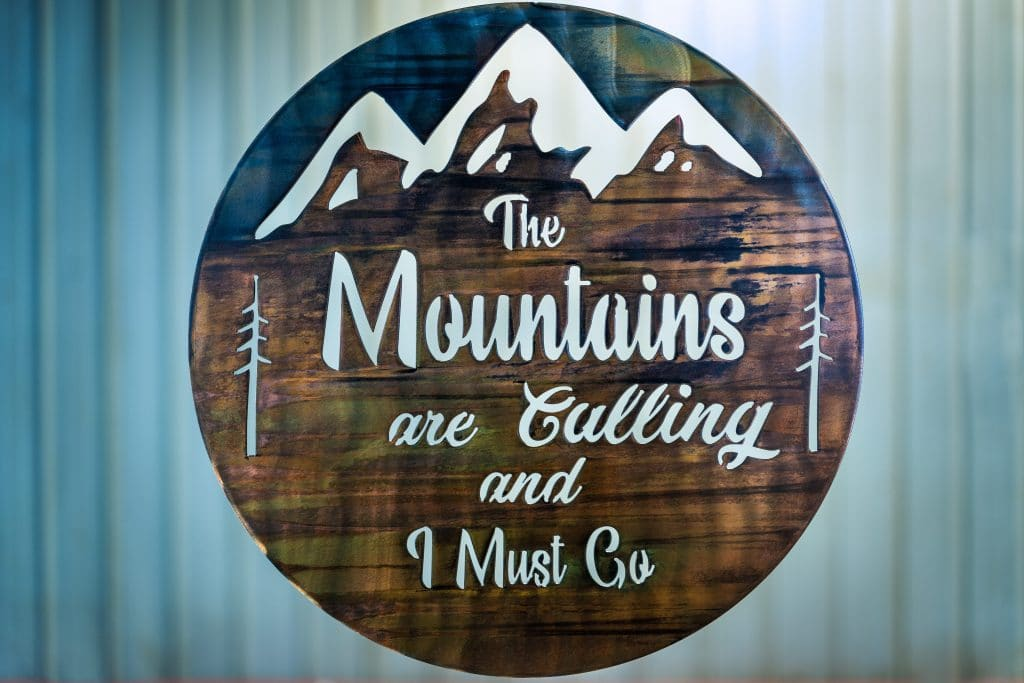 The Mountains are calling and I must go metal wall art is a circular piece of metal with the phrase cut into the metal with mountains in the background.