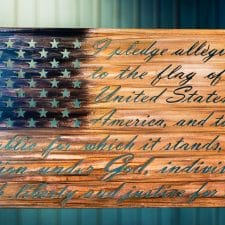 The American Flag metal wall decor with the Pledge of Allegiance cut into the metal. The metal is hand finished and has been coated with a multicolor patina to highlight the blue around the stars and woodgrain for the stripes.