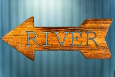 Metal wall art of River directional sign - Left facing - with metal shaped arrow with Lake cut into the middle. This piece has a wood grain copper patina finish.