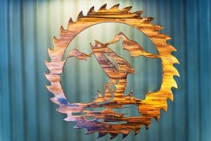Metal wall art cut out of a saw blade shape depicting at trout jumping out of the water with a mountain in the background inside the saw blade. This has a Wood Grain Copper Patina finish with some Multi-Color elements