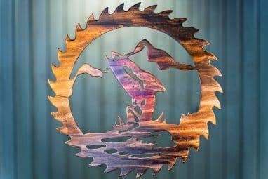 Metal wall art cut out of a saw blade shape depicting at trout jumping out of the water with a mountain in the background inside the saw blade. This has a Multi-Color Patina finish with deep blues and purples along side wood grain copper effects.