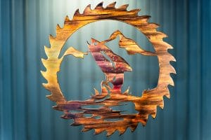 Metal wall art cut out of a saw blade shape depicting at trout jumping out of the water with a mountain in the background inside the saw blade. This has a wood grain copper patina with some multi-color effects.