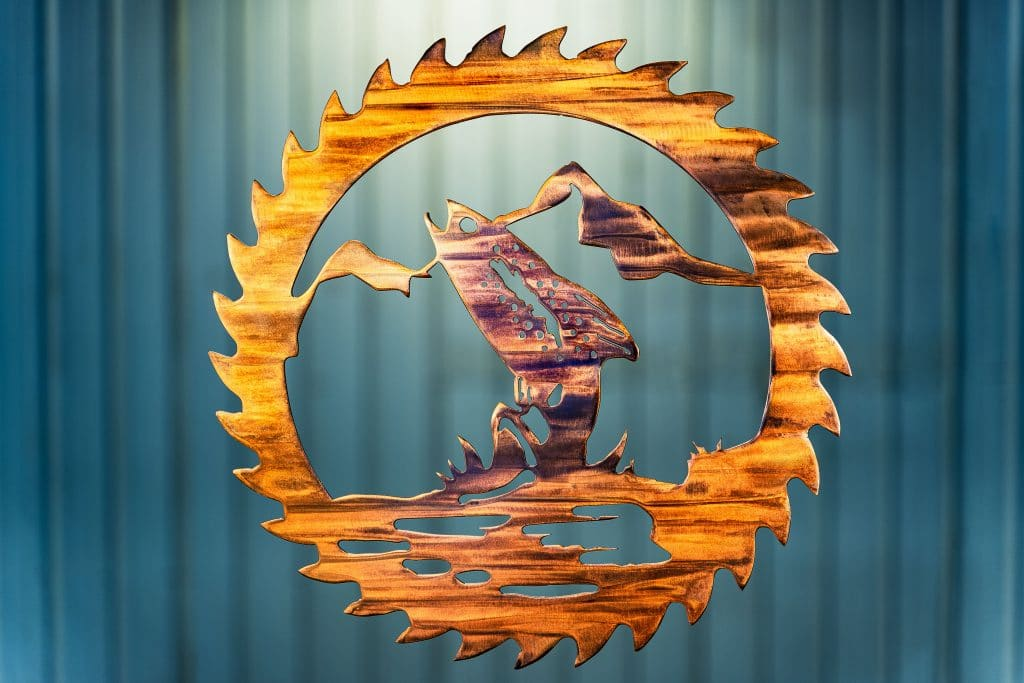 Metal wall art cut out of a saw blade shape depicting at trout jumping out of the water with a mountain in the background inside the saw blade. This has a Wood Grain Copper finish.