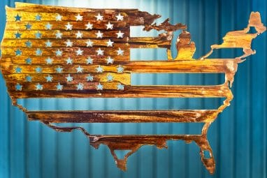 Metal wall art depicting American Flag inside outline of United States cut out of metal finished with Wood Grain Copper Patina