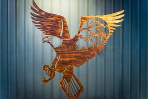 Metal wall art of American Bald Eagle with expanded wings and fish in talons all cut out of metal with a Wood Grain Copper Patina. There is also a portrait of a bald eagle in the right week cut out of metal.