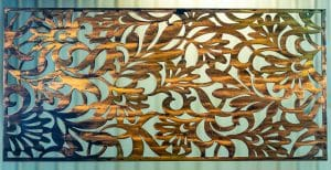 Metal wall art screen with floral pattern cut out of metal on wood grain copper patina finish