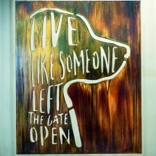 Live Like Someone Let The Gate Open metal wall decor depicts the saying next to a silhouette of a dog