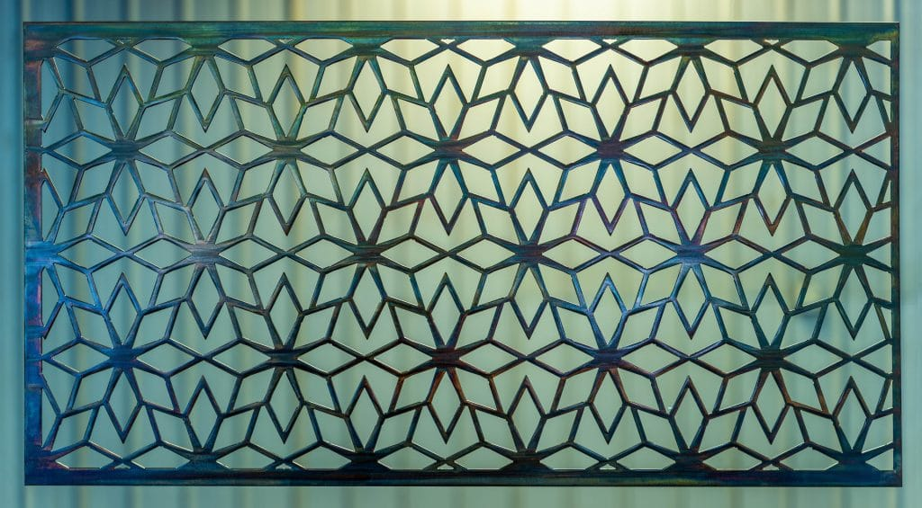 Geometric Metal Art Screen wall decor has flower patterns in a geometric shape.