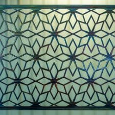 Geometric Metal Art Screen wall decor has flower patterns in a geometric shape.