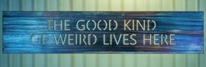 Good Kind of Weird Lives Here metal wall art has a wood grain copper patina.