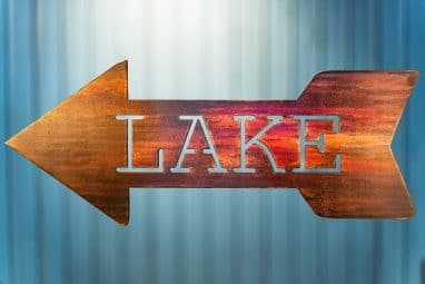 Metal wall art of Lake directional sign - Left facing - with metal shaped arrow with Lake cut into the middle. This piece has a wood grain copper patina finish.