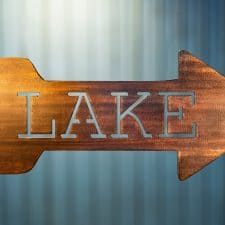 Metal wall art of Lake directional sign - Right facing - with metal shaped arrow with Lake cut into the middle. This piece has a wood grain copper patina finish.