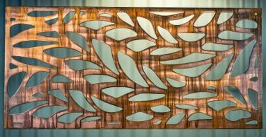 Metal wall art screen with long leaf pattern cut out of metal on wood grain copper patina finish