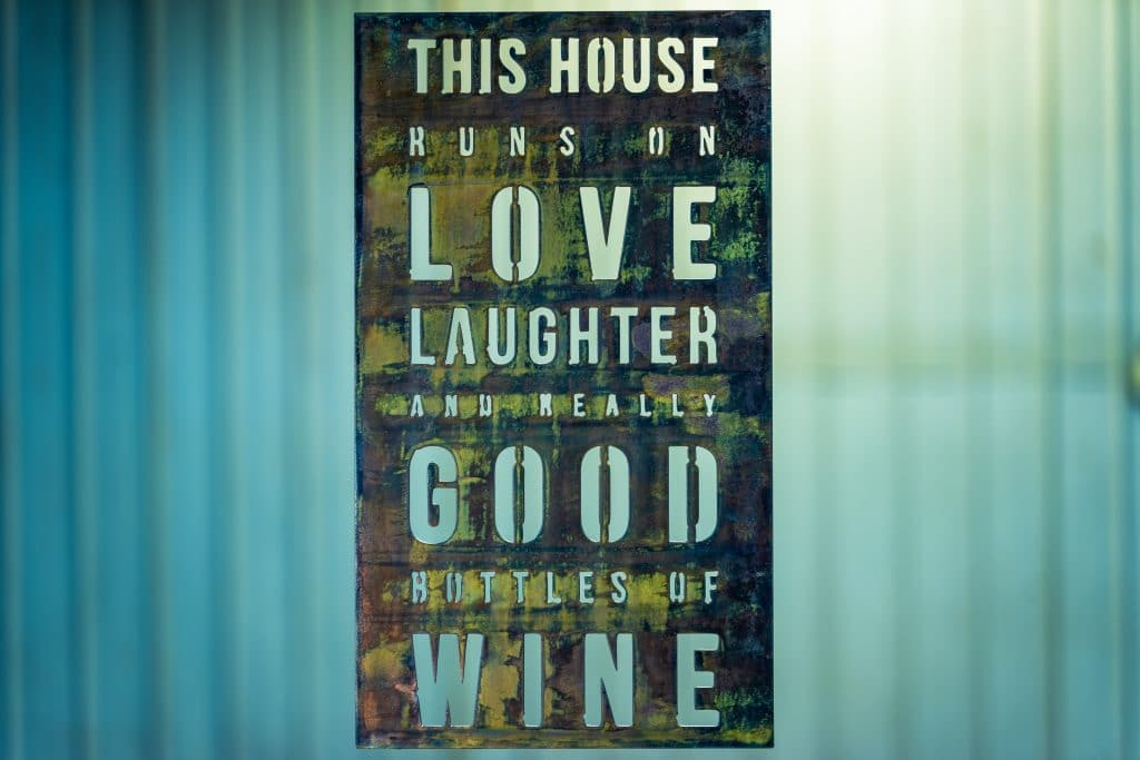 Metal wall art sign saying This House Runs on Love, Laughter and Really Good Bottles of Wine
