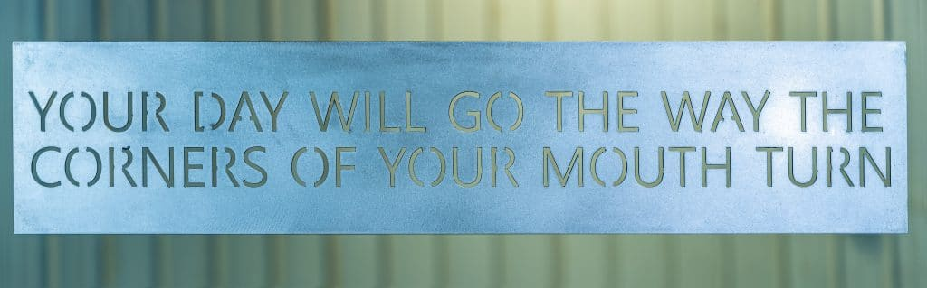 Metal wall art with Your Day Will Go The Way the Corners of Your Mouth Turn saying cut into metal