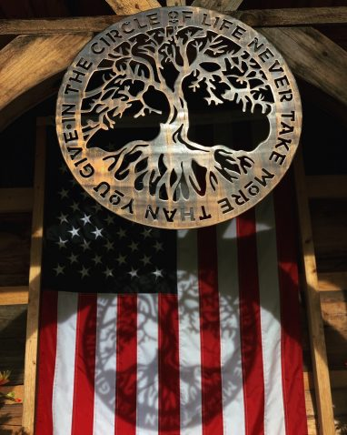 Circular metal wall art with a tree in the middle and the phrase In The Circle of Life Never Give More Than You Take. This picture shows the metal wall art projecting a shadow of the design onto an American Flag