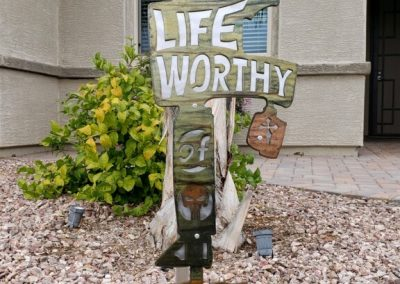 """Metal art of military field cross featuring boots, rifle and helmet with """"Living a life worthy of their sacrifice"""" quote cut into the metal."""