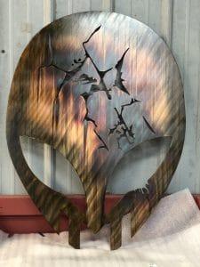 Custom metal wall art of alien-like helmet with cracks from battle