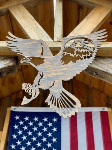 Metal wall art of American Bald Eagle with expanded wings and fish in talons all cut out of metal with a Wood Grain Copper Patina. There is also a portrait of a bald eagle in the right week cut out of metal. This picture shows the metal wall decor hanging on a cabin with an American flag in the background