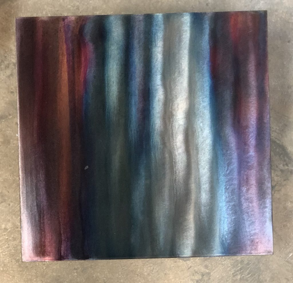 Sample photo of a multi-color patina finish from Artful MetalWorx metal art. The metal has a bright silver look that accents the polished steel showing the grinder marks where the metal was hand finished.