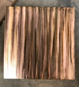 Sample photo of a wood grain copper patina finish from Artful MetalWorx metal art. The metal has a bright silver look that accents the polished steel showing the grinder marks where the metal was hand finished.