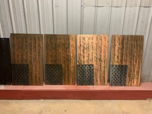 The American Flag metal wall decor with the Pledge of Allegiance cut into the metal. The metal is hand finished and has been coated with a multicolor patina to highlight the blue around the stars and woodgrain for the stripes. This picture shows four Pledge Flags lined up at the shop.