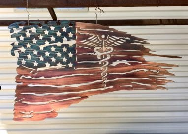 The New Battlefield Tattered Flag metal art depicts a ragged version of the American flag with the medical caduceus symbol in the flag