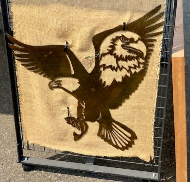 Metal wall art of American Bald Eagle with expanded wings and fish in talons all cut out of metal with a Wood Grain Copper Patina. There is also a portrait of a bald eagle in the right week cut out of metal. This picture shows the metal wall decor hanging on a cabin with an American flag in the background. This picture shows the piece at a festival.