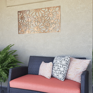 Metal Art Wall Decor rectangular Screen with Daisy pattern and a wood grain copper patina. This photo showcases the metal screen outdoor on a patio next to outdoor furniture and plant.